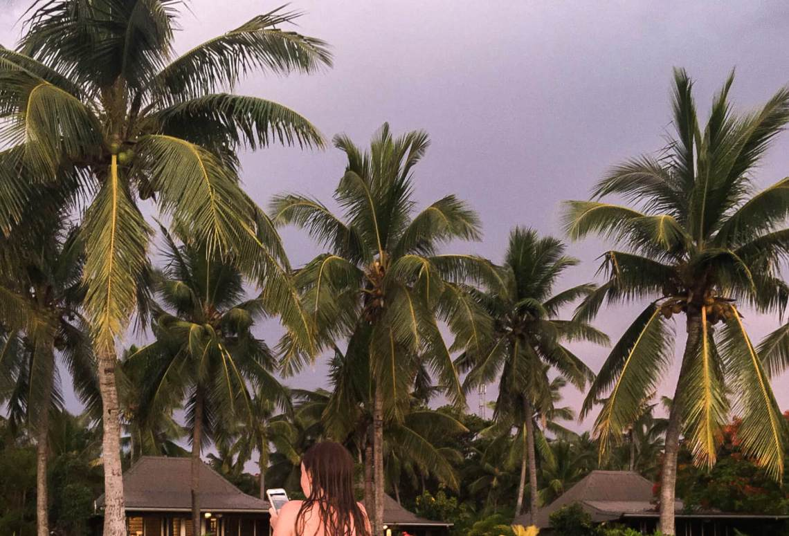 Girl looking down at her phone in front of palm trees and huts - with very rainy, dark sky above