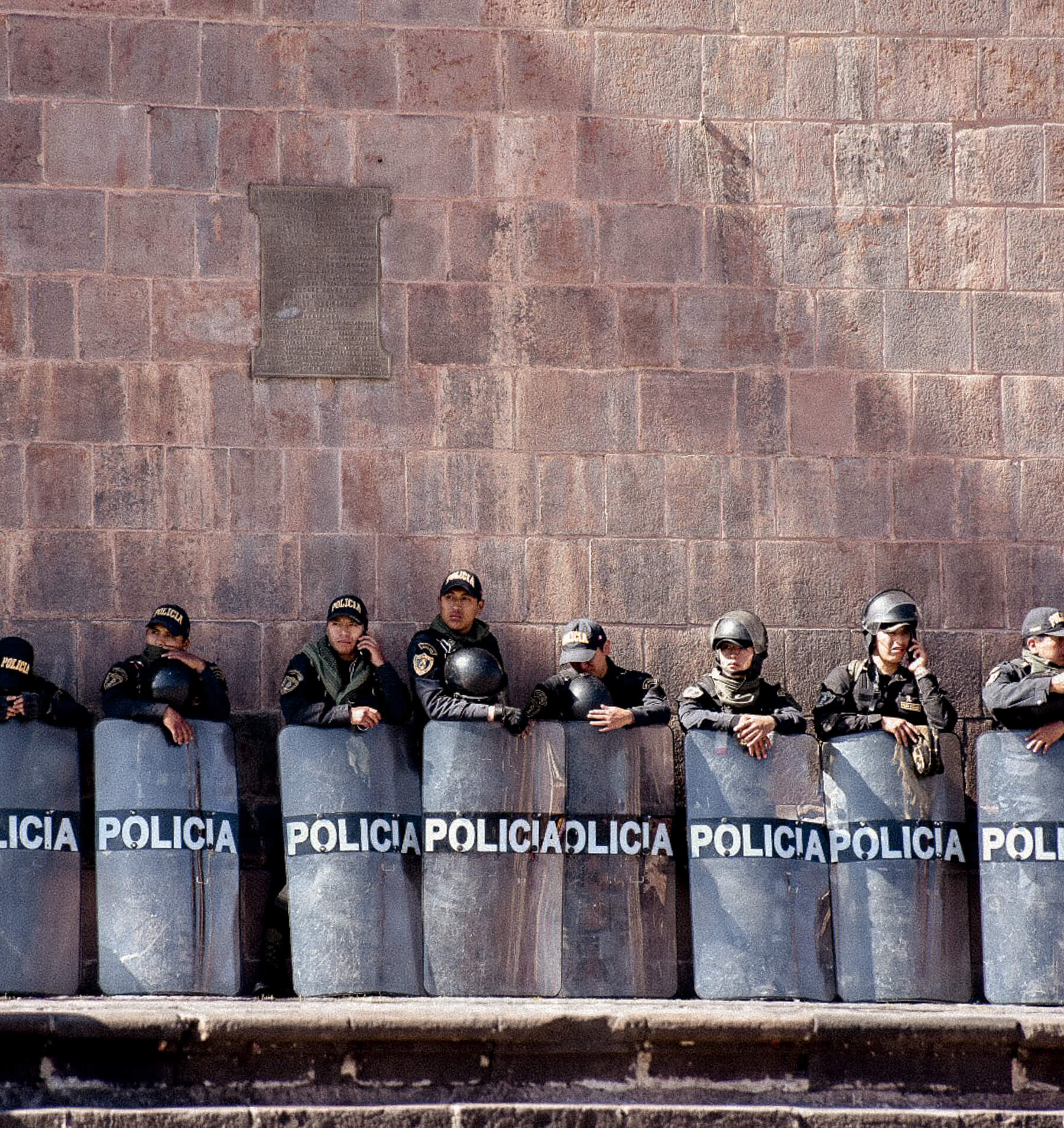 Police officers standing behind shields during 2017 teachers strike in Cusco