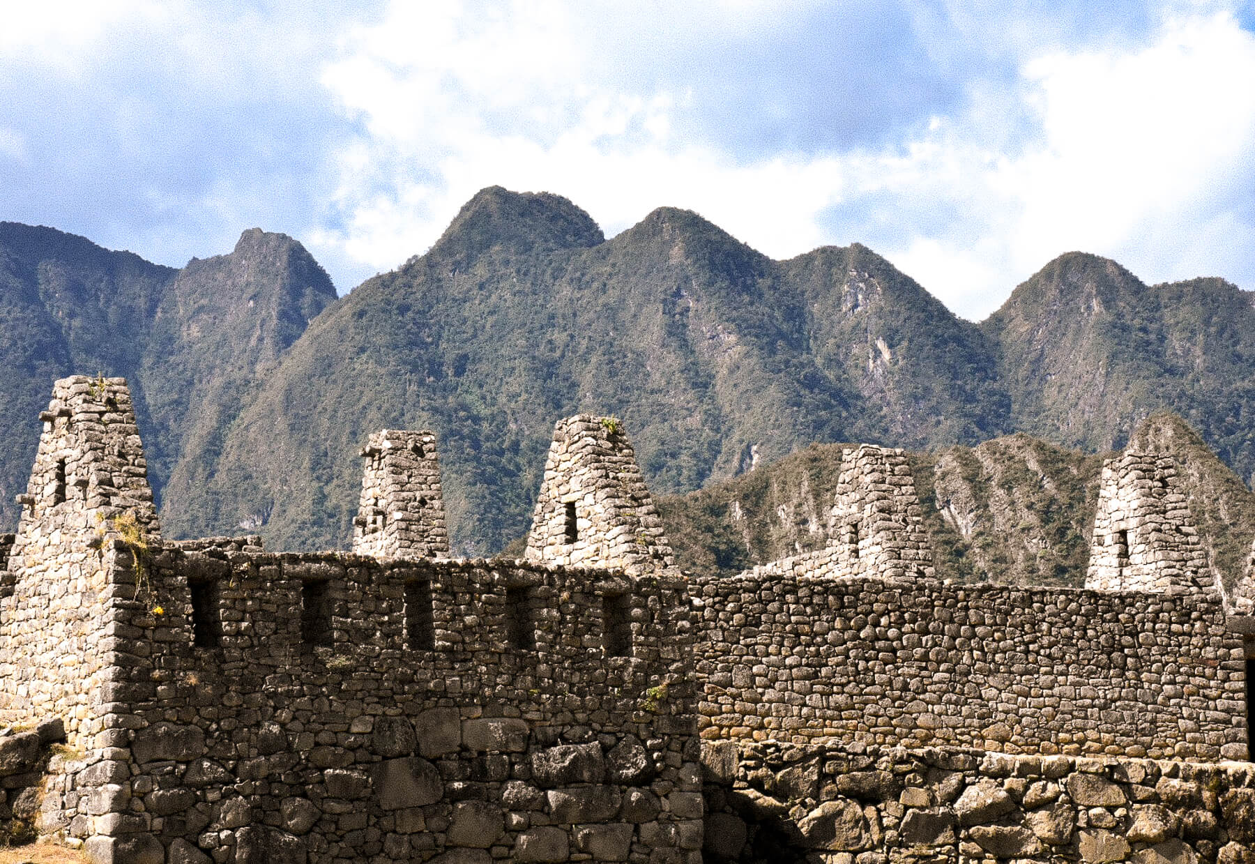 Looking over the top of stone ruins with the huge mountains towering behind them