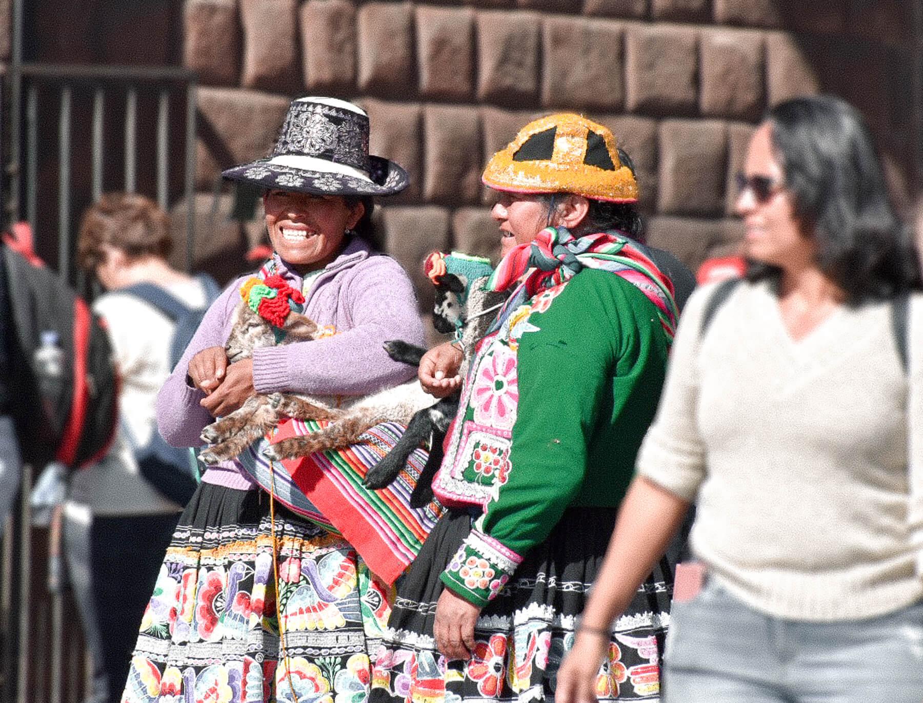 2 smiling Peruvian ladies chatting and holding baby llamas