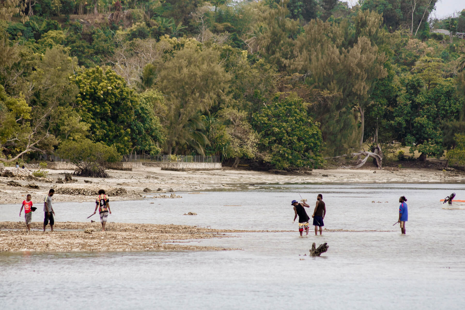A wide image of the nearby Vanuatu locals fishing and having fun on a beach