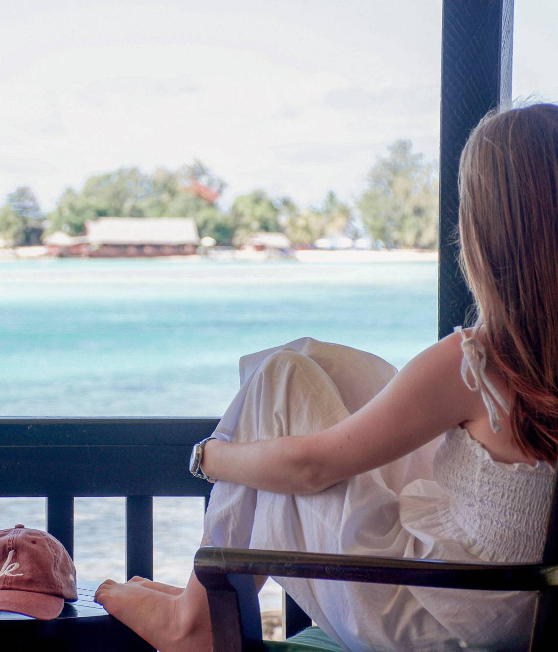A girl sitting at her deck overlooking the ocean with an island in the distance