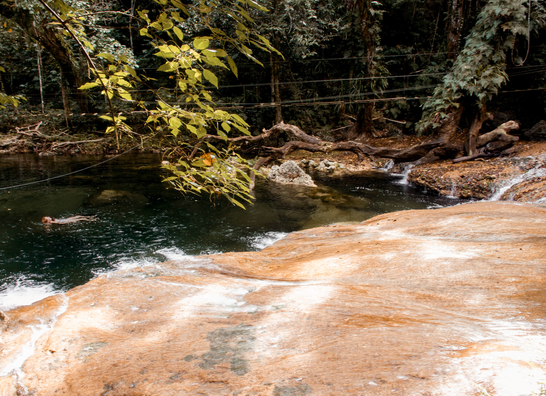 A girl laying on her back in the water of a forest swimming hole - Eden on the River