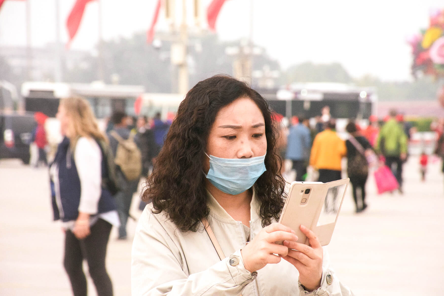A Chinese woman looking at her phone whilst wearing a light blue face mask