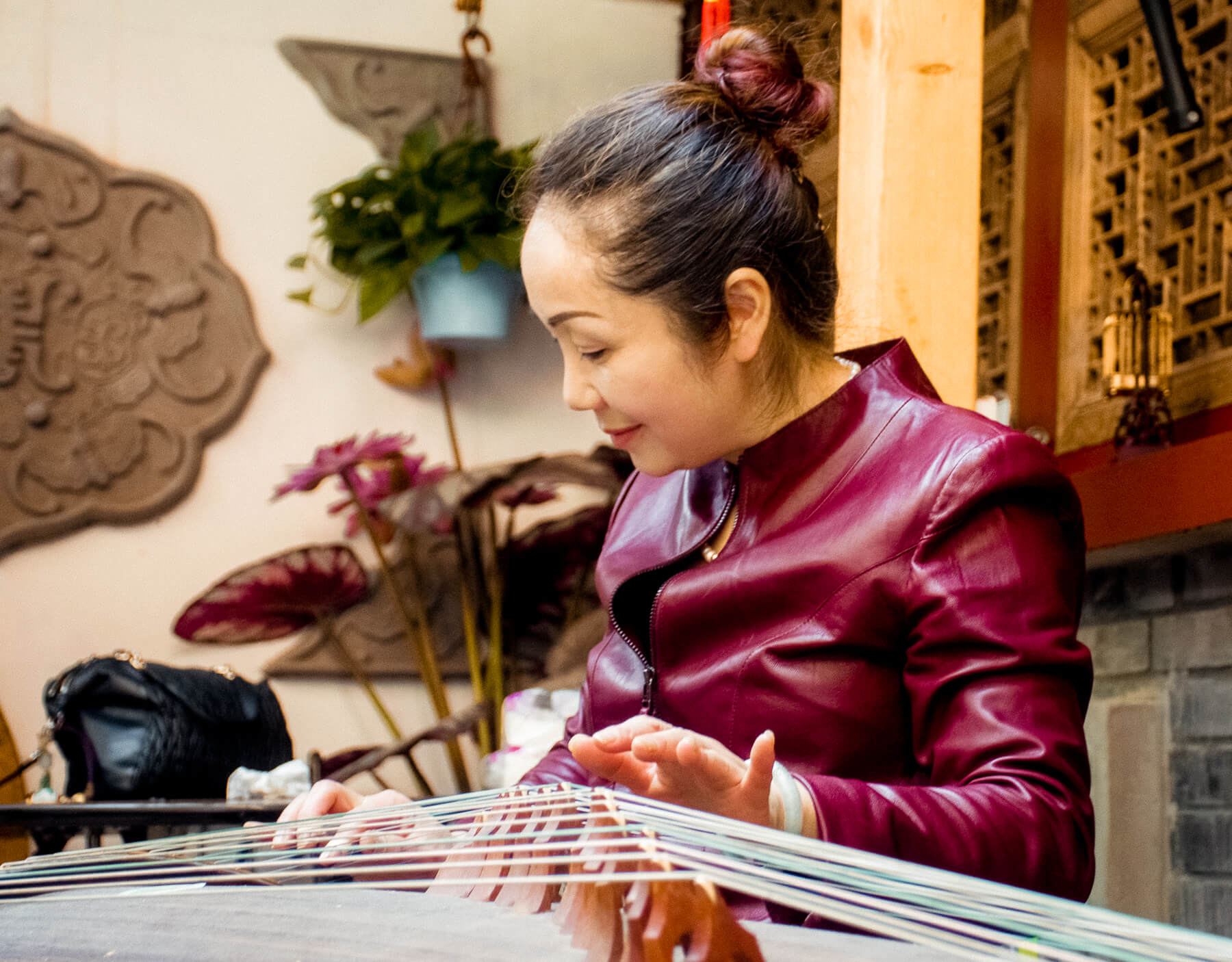 A Chinese lady playing the Guzheng (traditional Chinese harp)
