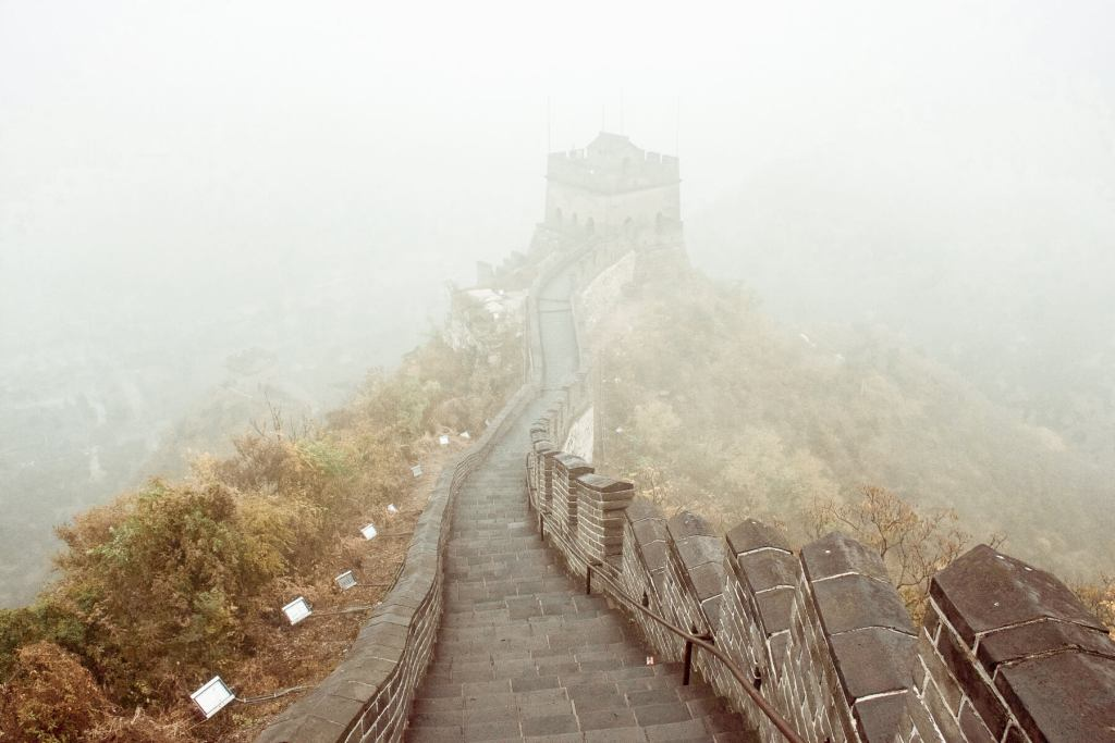 Looking along the path of the Great Wall of China, at the top of a hill in the fog
