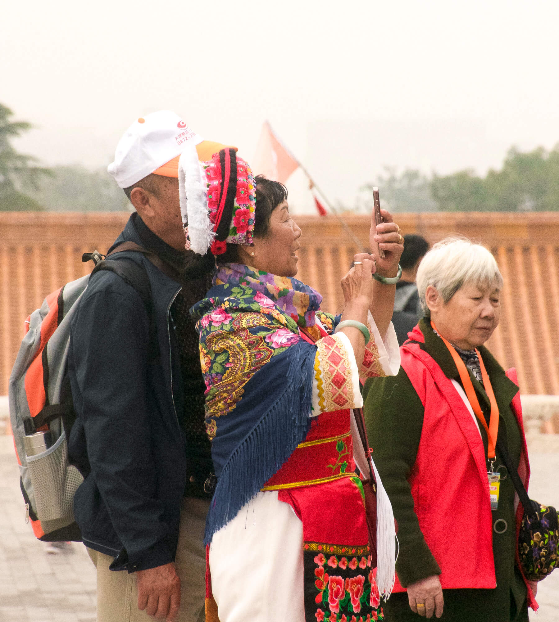 A woman dressed in traditional Chinese clothing, taking a selfie with a local man