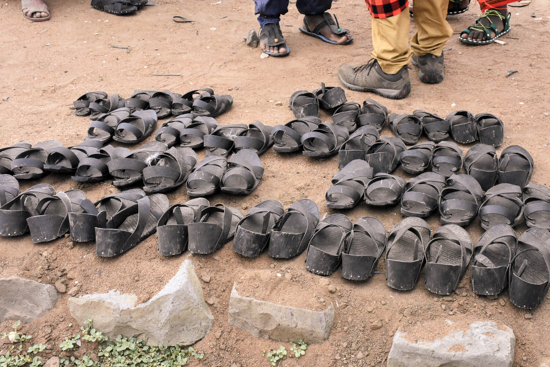 A huge selection of shoes in a market, made from tyres