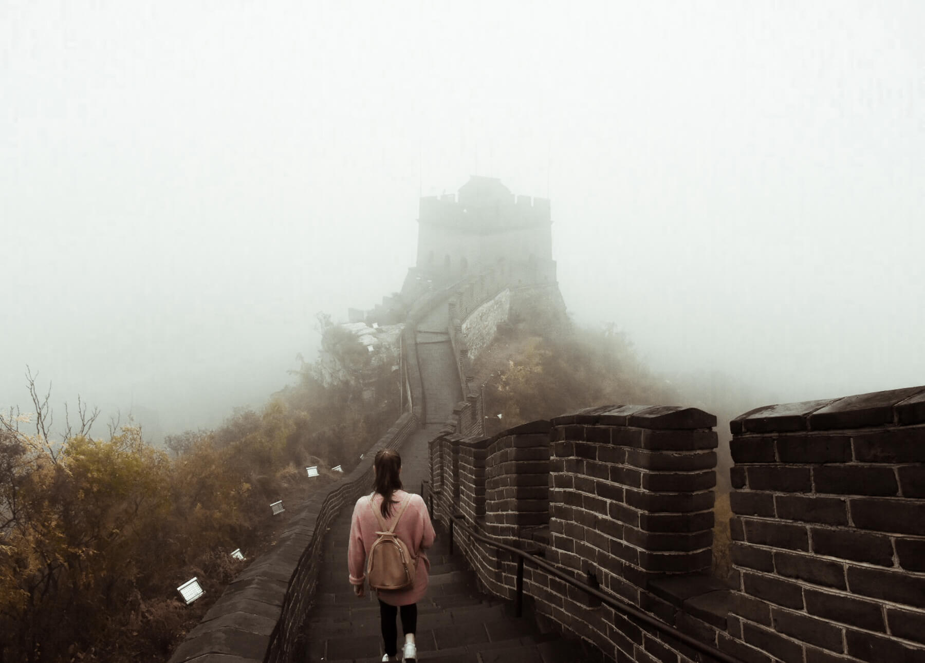 A young girl with red hair, walking the Great Wall of China high up in the mountain