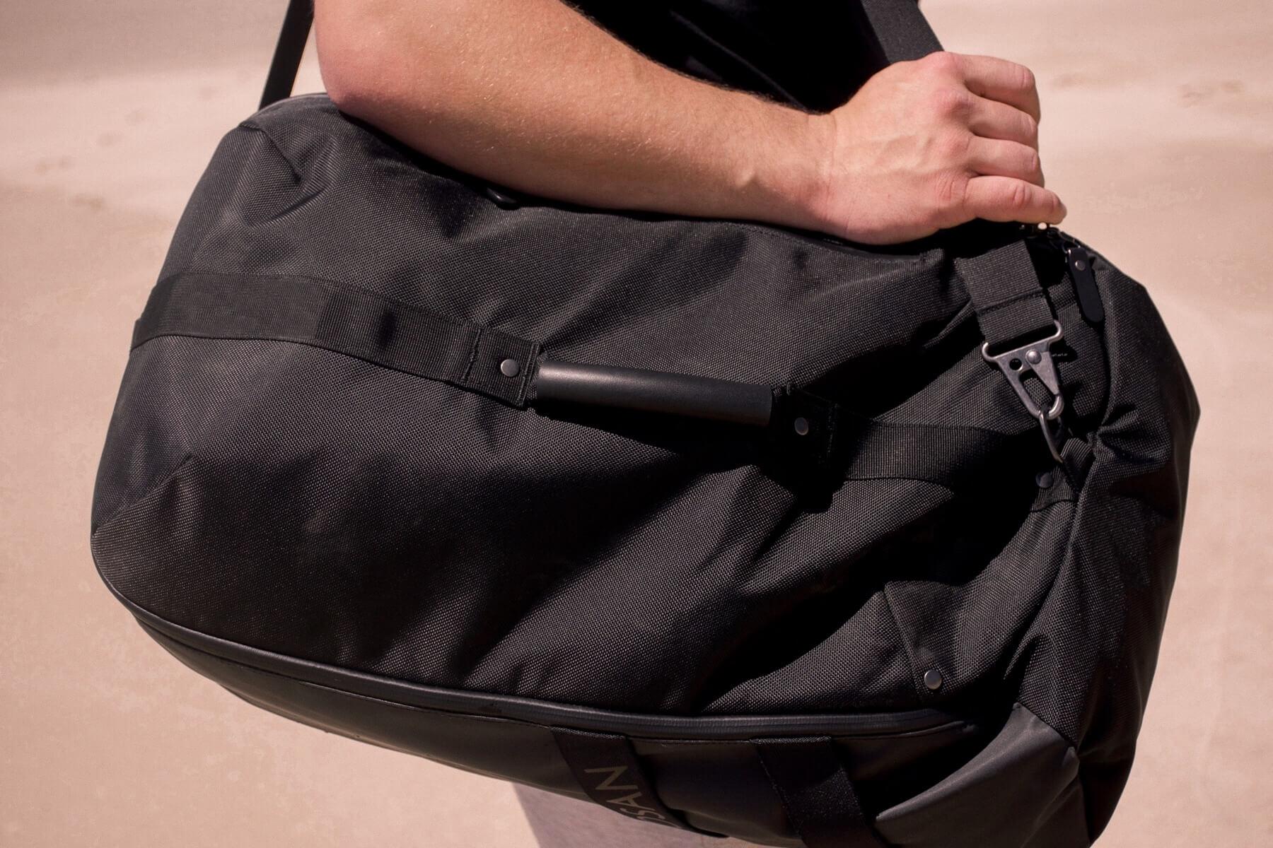 Close up of a man carrying a big black duffle bag over his shoulder