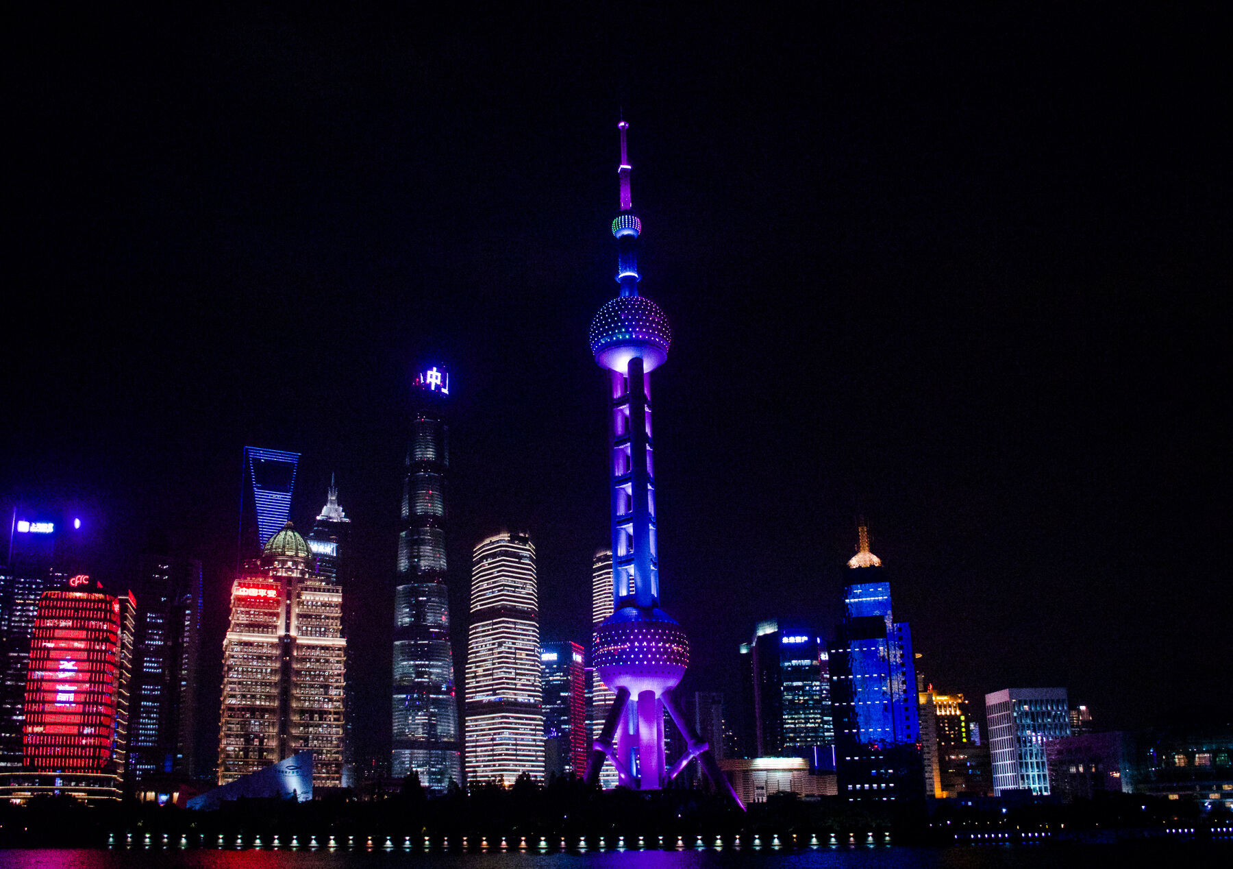 The high rise buildings in Shanghai at night time, all lit up in different colours