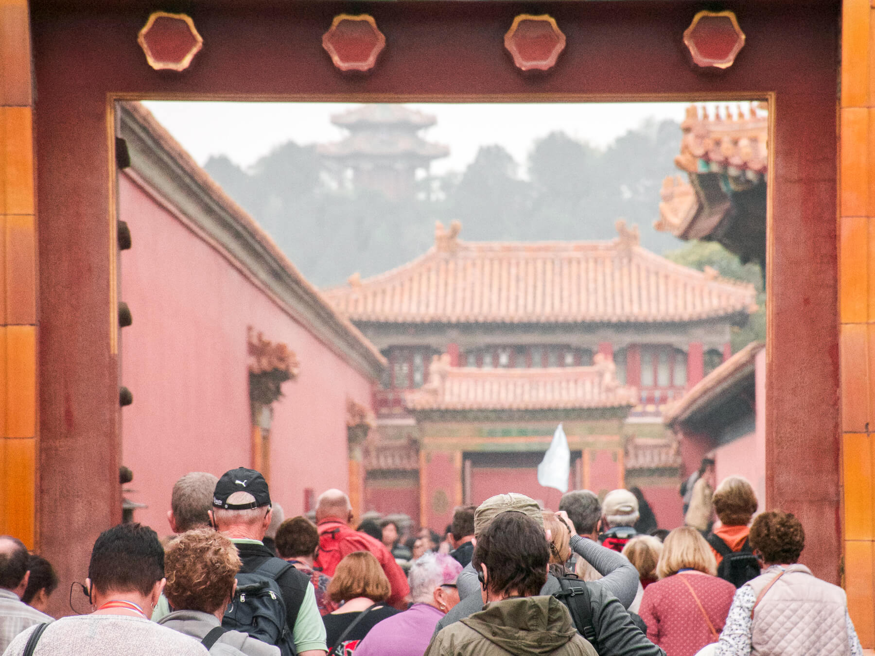 A group of tourists from Trip A Deal, following a blue flag through the Forbidden City