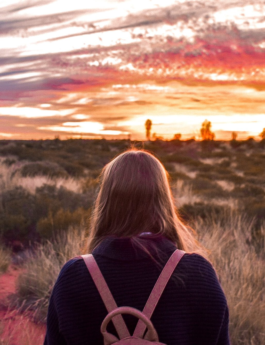 Girl facing towards outback looking into the sunset