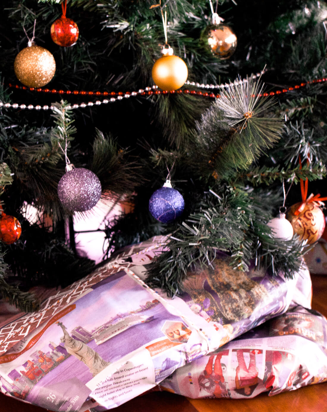 Presents under a Christmas tree wrapped in eco friendly recyclable christmas paper