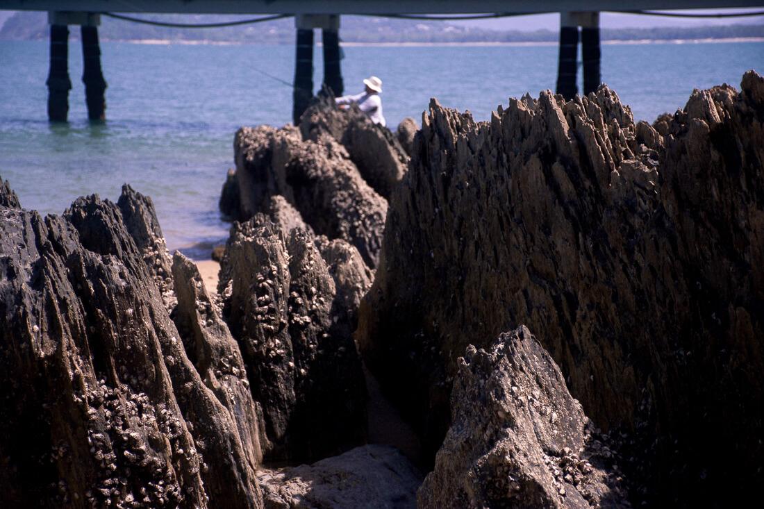 Man fishing on Palm Beach amongst the rocks