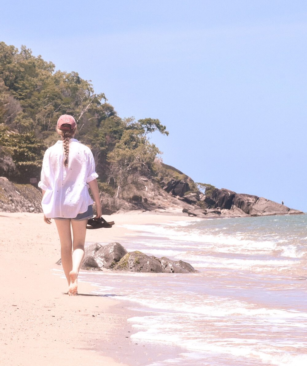 Girl walking along beach at Palm Cove, Queensland