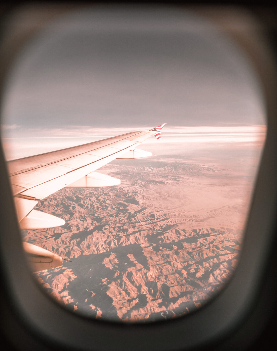 View of aeroplane wing framed by the circle window