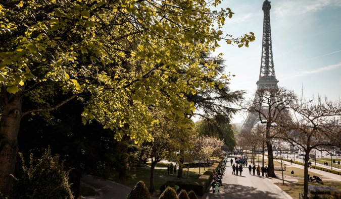 Walking down a path surrouned by trees near the Eiffel Tower in Paris, France