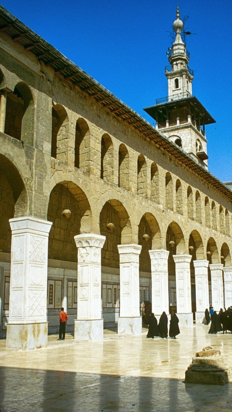 White multilevel minaret pillar behind a wall of double brown stone arches and white pillars in Umayyad Mosque, also known as the Great Mosque of Damascus in Syria.