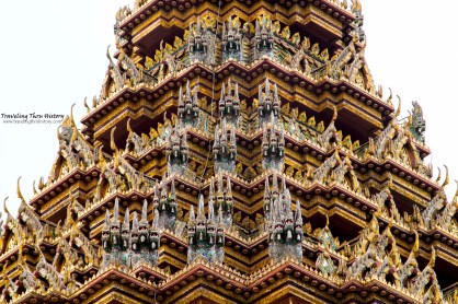 Close-up of the roof of Phra Mondop. The embellishment of the roof is done using a form of Chinese broken-pottery artwork called chien-nien. Around the roof of Phra Mondop are multiple mini gables as well as miniature figures that are reminiscent of the Naga, the multi-headed serpent. The serpentine figures on the roof of Phra Mondop are attached to the roof via a bargeboard, which is a long, thin panel on the edge of the roof at the gable ends and are called lamyong. A lamyong is sculpted in an undulating, serpentine shape called nag sadung. The blade-like projection on top of its head is called a bai raka and represents both the naga fins and the feathers of Garuda. The piece projecting from the chin of the lamyong is called a hang hong, which usually takes the form of a naga's head turned up and facing away from the roof. The naga head may be styled in flame-like kranok motifs and may have multiple heads or it may just be one head.