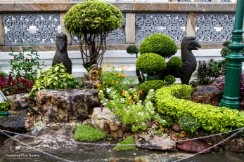 Small gardens with mythical creatures dot the landscape inside the Wat Phra Kaew complex