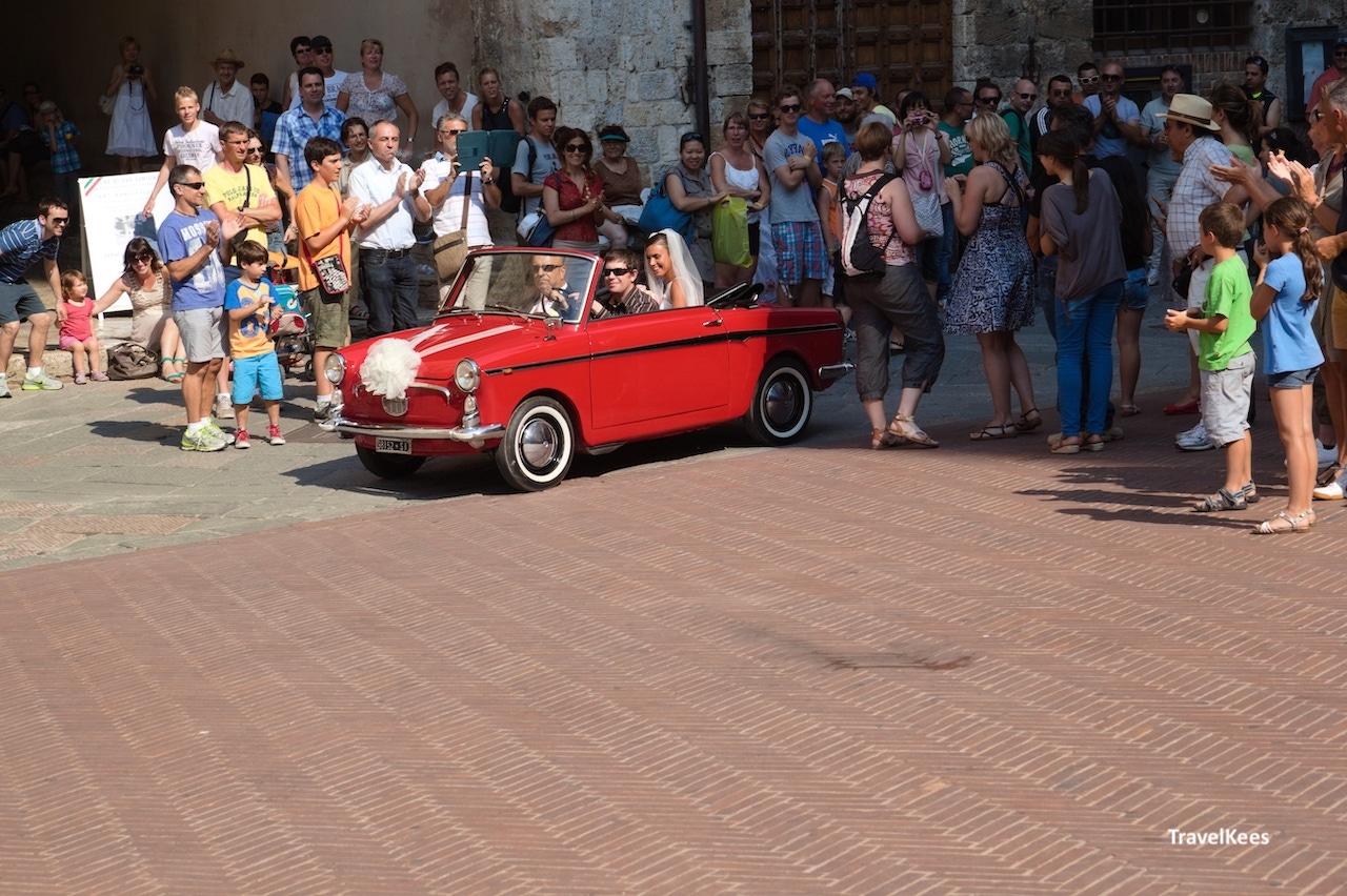toscaanse bruiloft, klein rood autootje met bruidspaar
