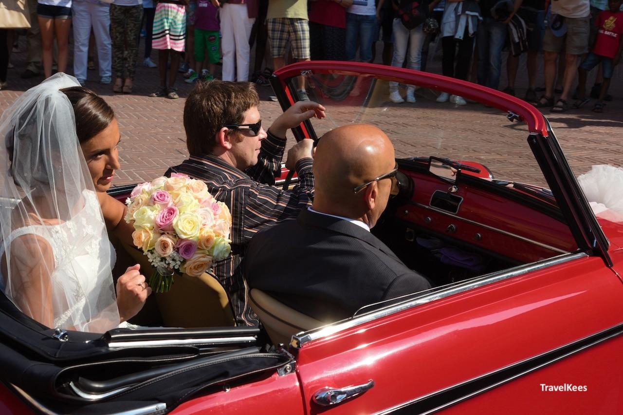 klein rood autootje met bruidspaar