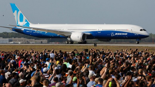 Boeing employees raise up their camera phones to record the first test flight of the new Boeing 787-10 Dreamliner as it ...