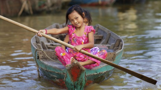 Children in a rowing boat on Tonle Sap Lake in Siem Reap, Cambodia.
