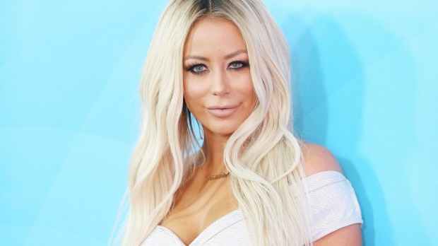 Aubrey O'Day says that an American Airlines flight attendant had her shirt removed in front of the other passengers.