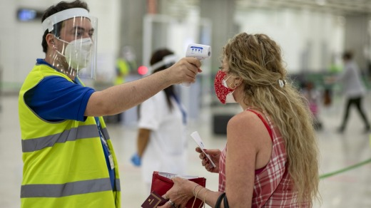 A passenger's temperature is checked at Madrid's airport. Even with a vaccine, travel is unlikely to return to how it ...
