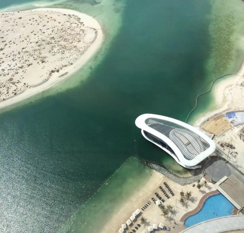 spiaggia con ombrelloni e lettini con accanto una piscina ed una grande costruzione bianca che si affaccia sul mare di colore verde