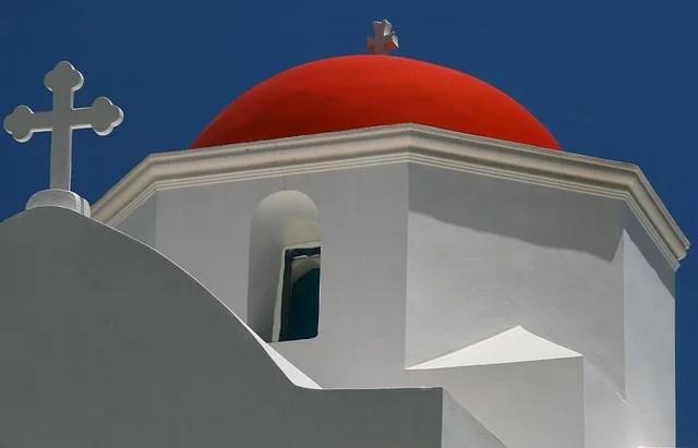 chiesa bianca con tetto rosso in stile greco con croce sulla cupola