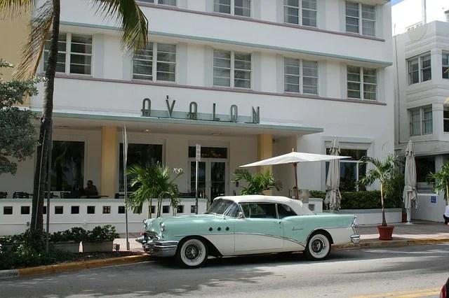 auto d'epoca di fronte ad un hotel con il nome riportato sopra l'ingresso