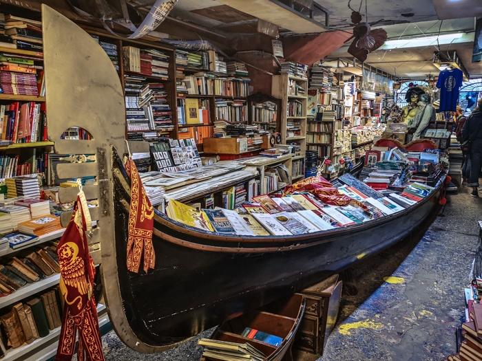 the gondola of Libreria Acqua Alta in Venice Italy, full to the brim with books to buy.