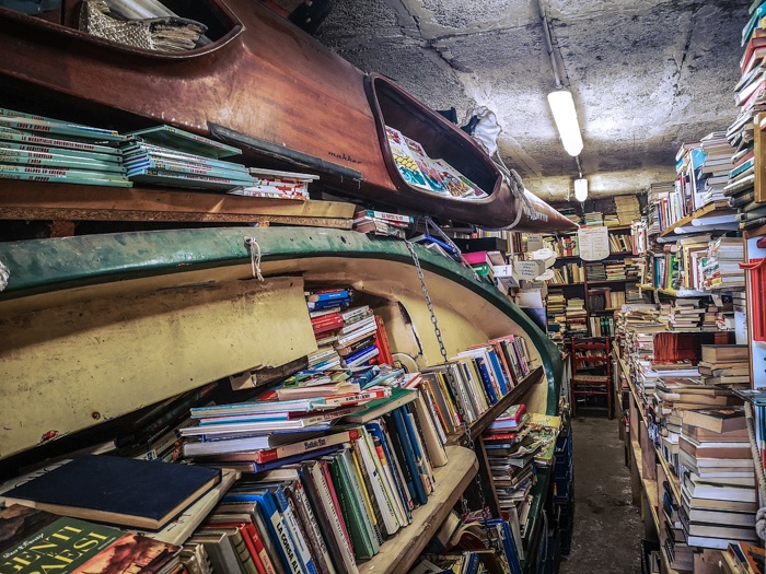 the boats of Libreria Acqua Alta Bookshop in Venice Italy has boats, kayaks and even bathtubs full of books to prevent damage during the yearly rising of the waters (acqua alta)
