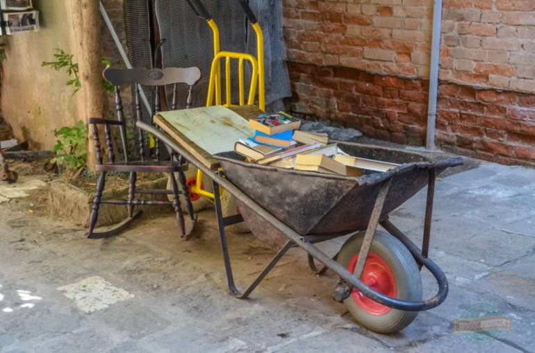Wheelbarrow and rocking chair outside bookshop in Venice Italy