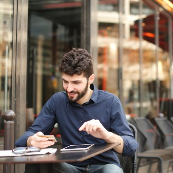 man making purchase on tablet at outdoor cafe