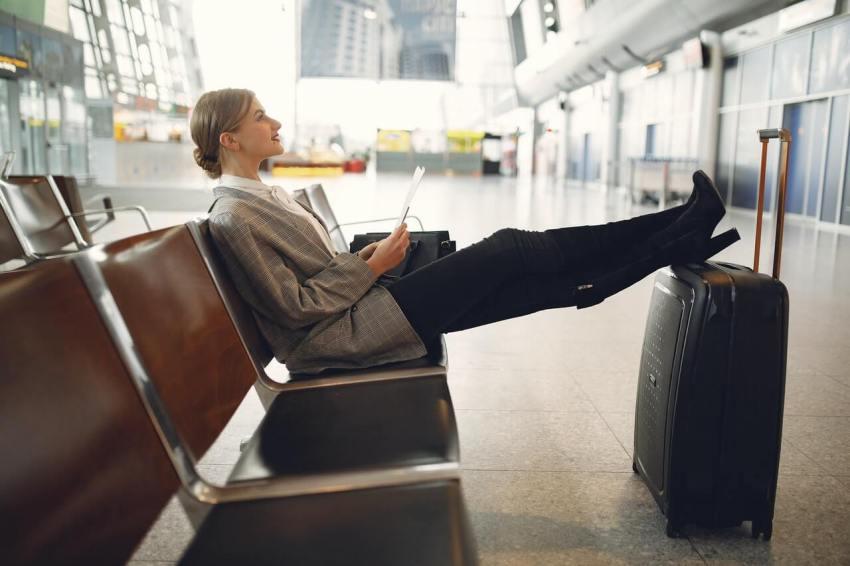 frau legt beine auf koffer