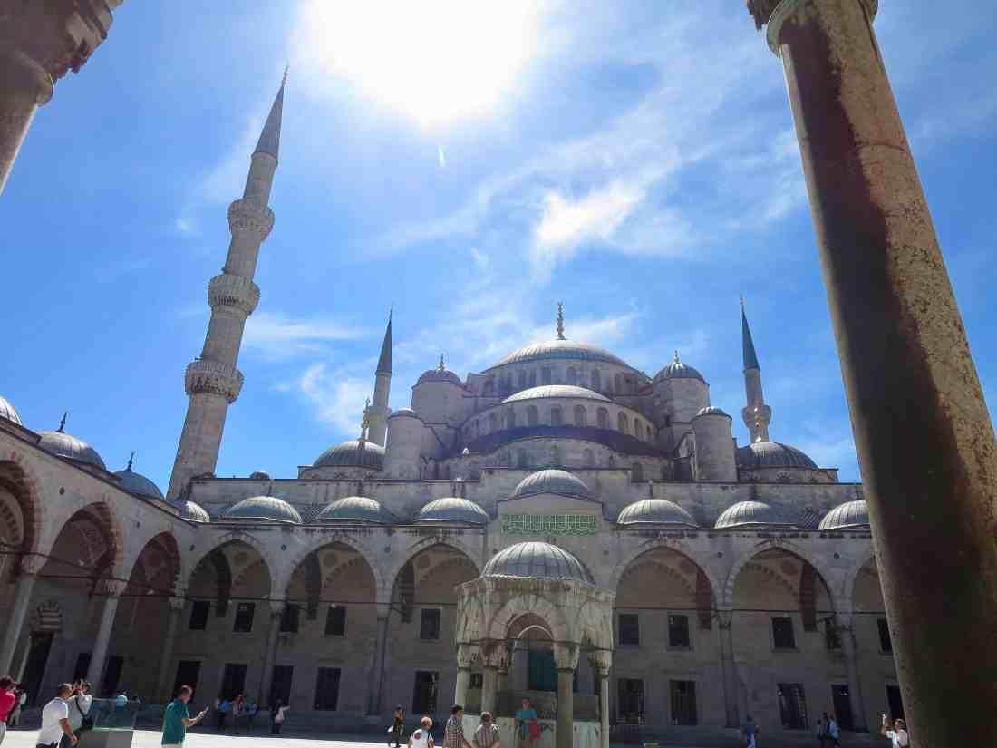 The Blue Mosque courtyard on a sunny day with tourists