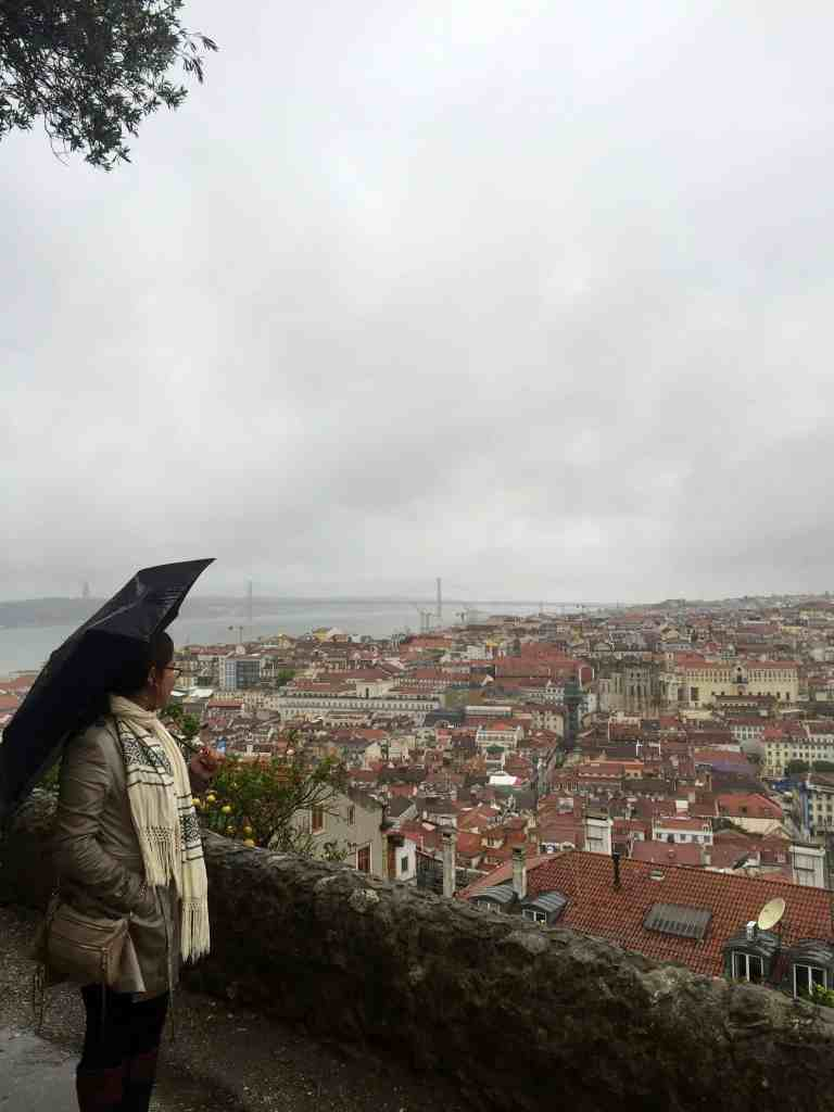 girl staring off into European city on a rainy day with a black umbrella
