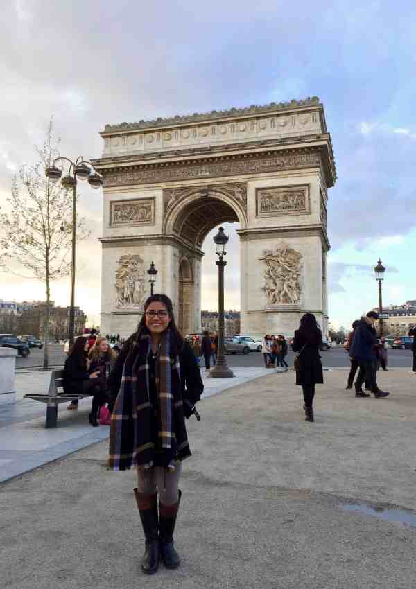 girl with glasses and black hair and scarf standing in front of the arc de triumph