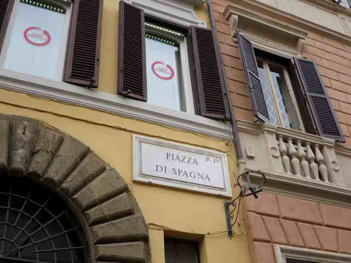 Italian building with a a sign saying piazza di spagna in rome, italy