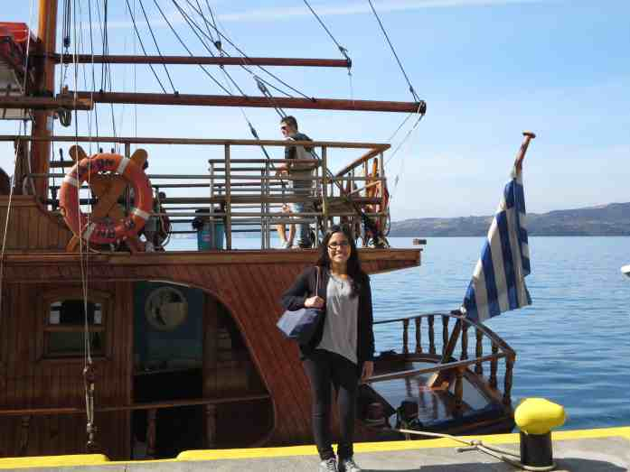girl standing in front of a boat with the Greek flag in Greece