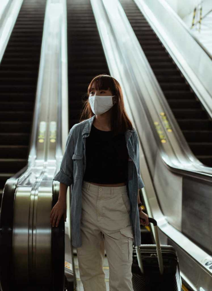 WOman with face mask and suitcase