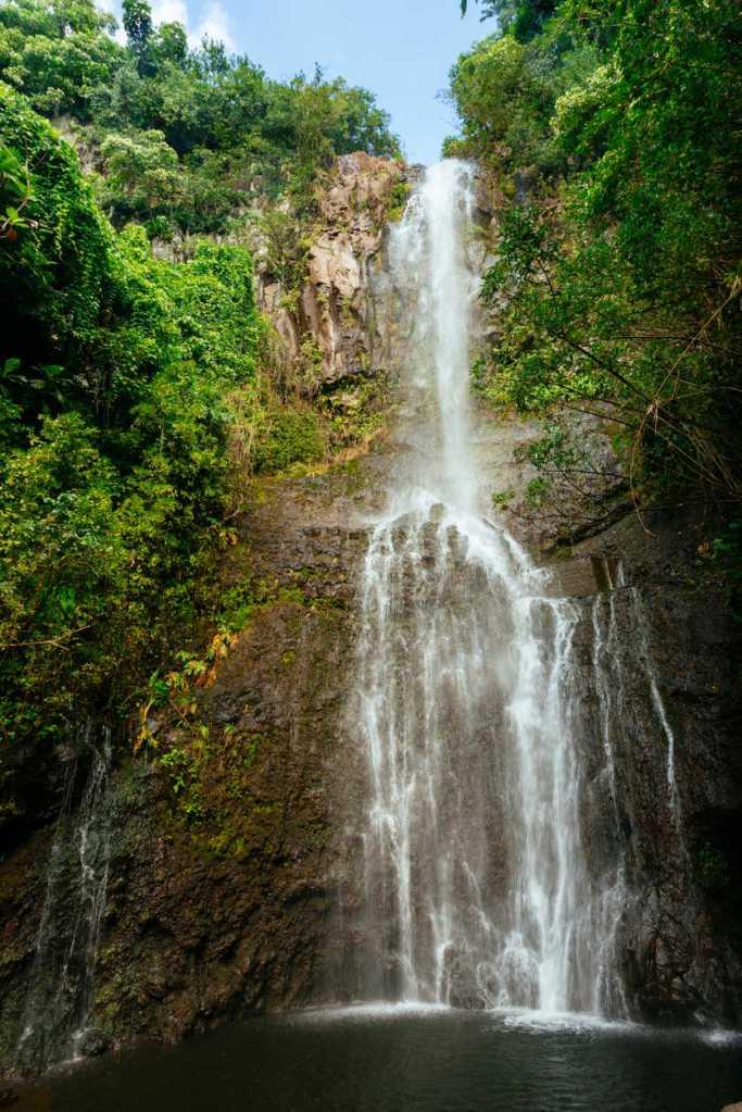 Wailua Falls waterfall on the edge of a rainforest covered volcanic mountainside on Maui, Hawaii.