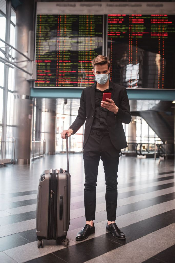 male traveler at the airport wearing a mask with his luggage