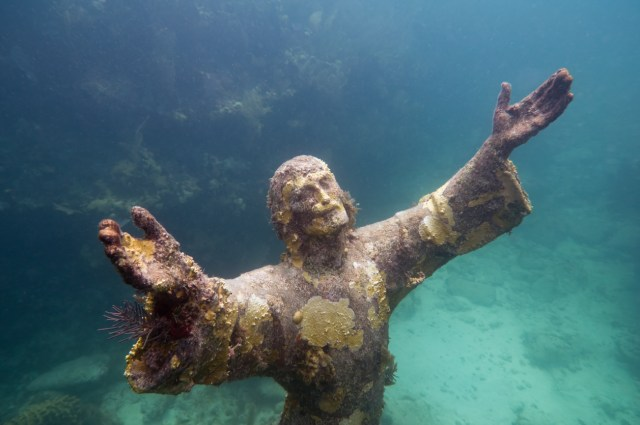 Christ of the abyss - religious underwater statue encrusted in corals, placed about 25 feet deep in John Pennekamp Coral Reef State Park in Florida Keys. Replica of the Italian sculpture. Wide angle, side flash and sunlight combined.