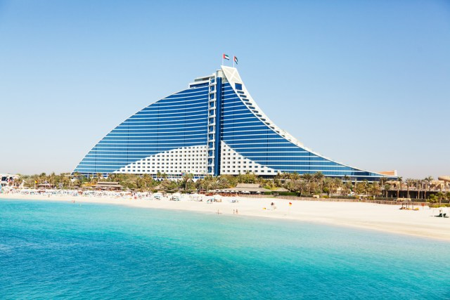 Dubai, United Arab Emirates - March 23, 2011 : Jumeirah Beach hotel with the pure white sand beach and crystal clear water in front of it surrounded by green palm trees. Voted the Best Hotel in the Middle East for two years in a row at the business Traveller Awards held in 2011 in Germany.