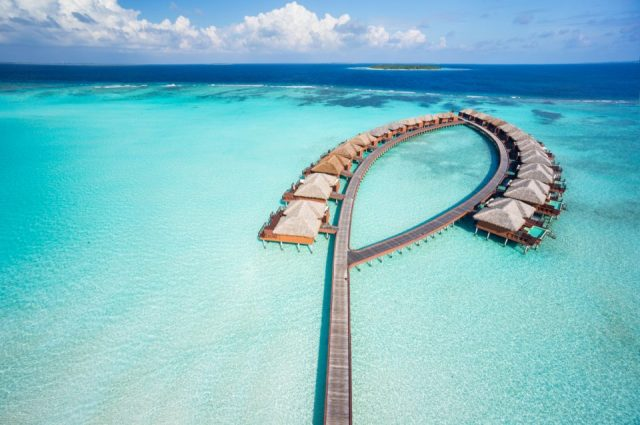 aerial view of luxury overwater villas in tropical lagoon of indian ocean